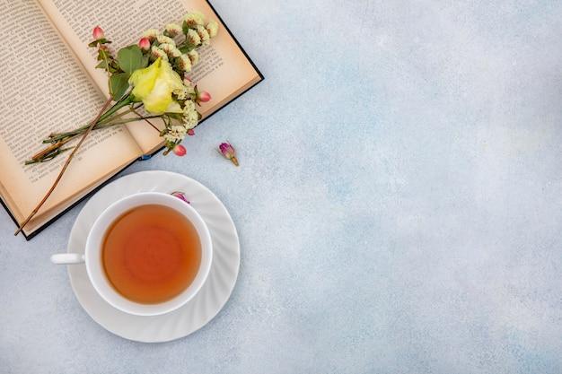 Вид сверху на чашку чая с желтой розой на белом с копией пространства