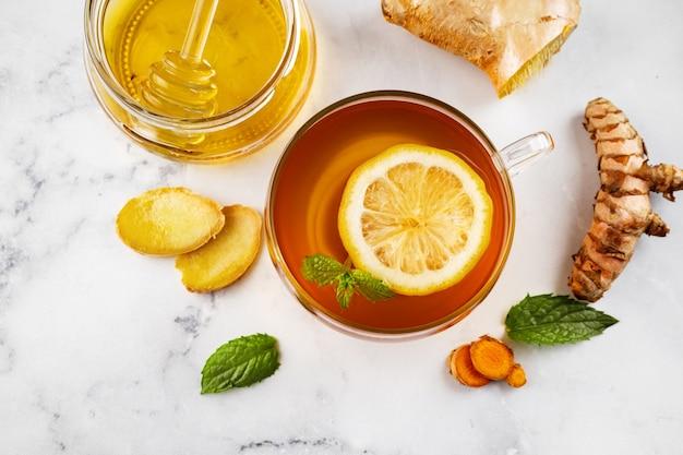 Вид сверху чашки имбирного чая с куркумой с ломтиком лимона, банкой меда и ингредиентами на белой поверхности. зимняя иммуностимулирующая пища