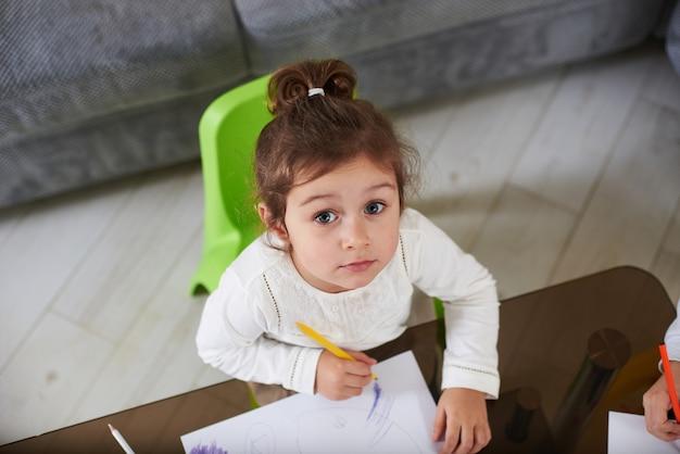 흰색 셔츠를 입고 카메라를보고 귀여운 유치원 여자의 상위 뷰. 사랑스러운 아기 소녀 실내 그리기.