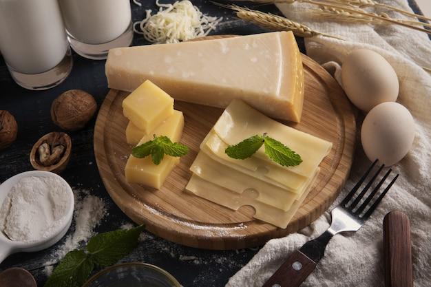 테이블에 우유, 밀가루, 계란이 있는 맛있는 치즈 플래터의 상단 보기