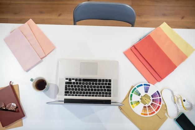 Вид сверху на стол в офисе с разными вещами, лежащими на нем