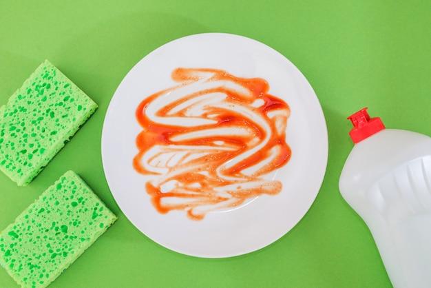 Вид сверху грязной тарелки, кухонной губки и моющего средства в бутылке на зеленом фоне.