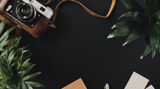 케이스에 들어있는 평평한 필름 카메라의 상위 뷰는 노트북과 펜 옆에있는 검은 색 테이블에 놓여 있습니다. 예술가 또는 사진 작가의 작업 공간 개념. 광고 공간