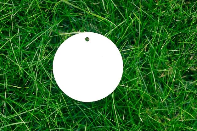 緑の春の草とロゴのコピースペースで販売されている1つの白い段ボールの丸いタグで作られたフレームの上面図。自然な概念。
