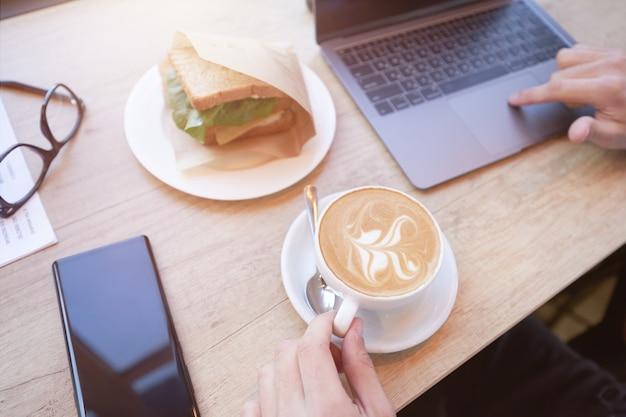 ラップトップを使用してコーヒーを飲みながら朝食をとっているフリーランサーやビジネスマンの上面図
