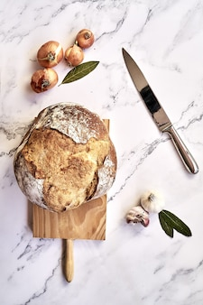 Вид сверху на свежеиспеченный традиционный хлеб на деревянной доске с луком, чесноком и ножом