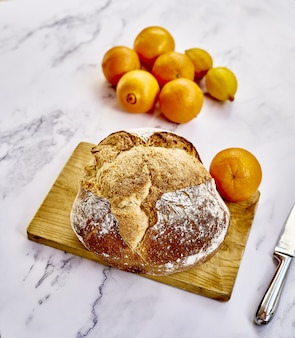 Вид сверху на свежеиспеченный традиционный хлеб с апельсинами, лимонами и ножом