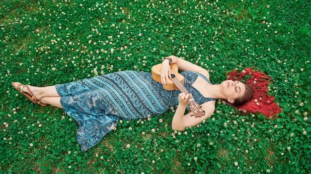 여름이면 풀밭에 누워 우쿨렐레를 연주하는 전신 여성, 풀밭에 흩어져 있는 빨간 머리, 눈을 감고 있는 모습.