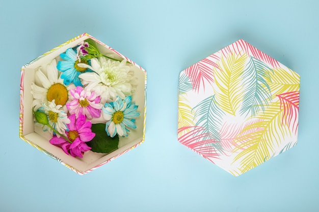 青の背景にデイジーとカラフルな菊の花でいっぱいのギフトボックスの平面図