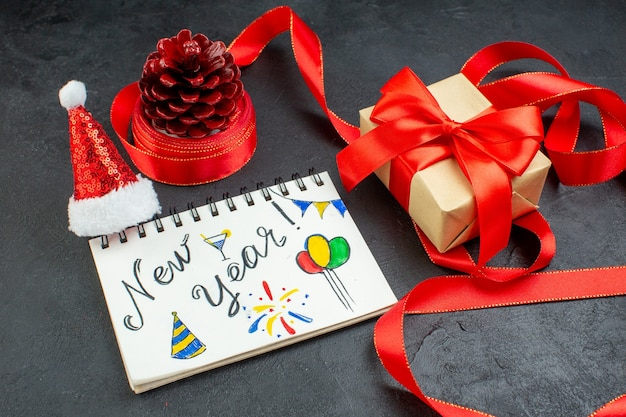 赤いリボンとノートブックと新年の書き込みと暗い背景の上のサンタクロースの帽子の美しいギフトとギフトの針葉樹の円錐形の上面図