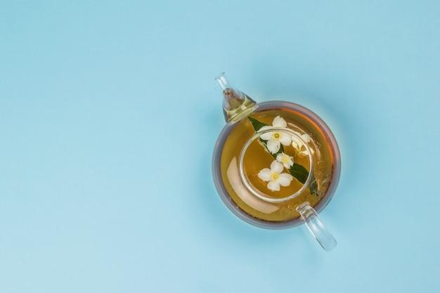 青い背景にジャスミン茶とガラスのティーポットの上面図。健康に良い爽快なドリンク。