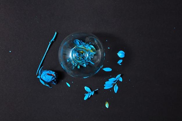 Вид сверху на стеклянную вазу с расписанным синим листом и сухой розой