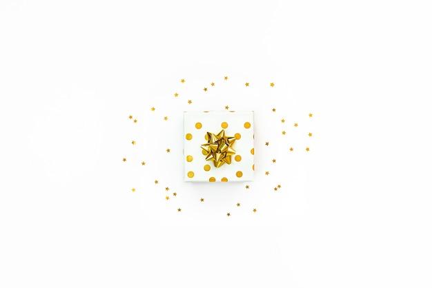 白い背景の上の金色の点線のギフトボックスと星型の金色のスパンコールの上面図。