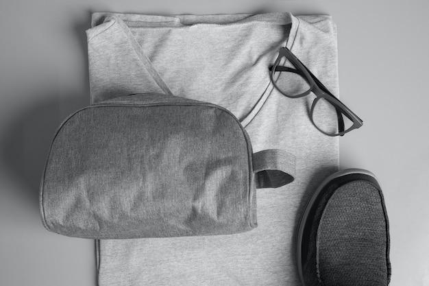 Вид сверху на серую мужскую модную футболку, очки, сумку для туалетных принадлежностей и кроссовки на сером