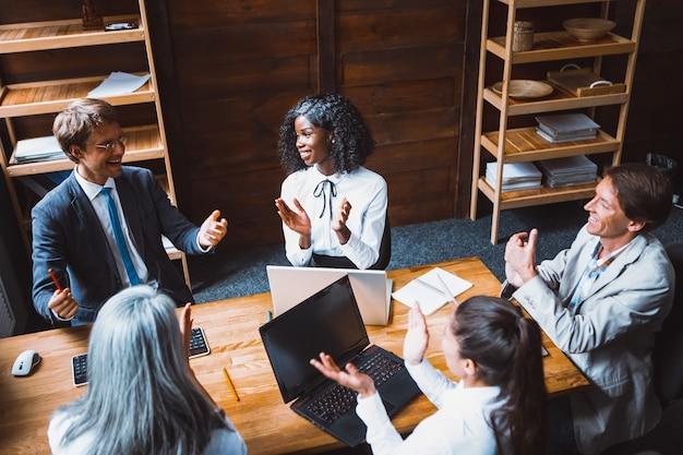 Вид сверху группы молодых многоэтнических деловых людей собрались вместе, чтобы создать проект. молодые фрилансеры в современном офисе со стойкой или стеллажами на фоне.