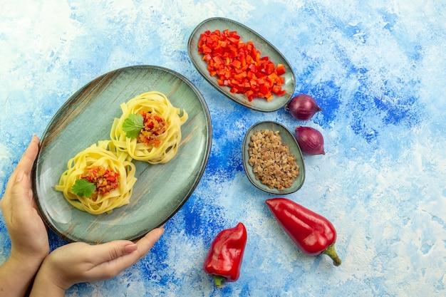 青いテーブルにおいしいパスタと必要な野菜の肉と青いプレートを持っている手の上面図