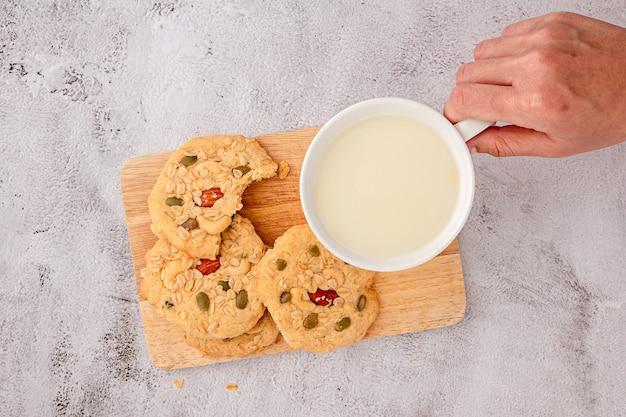 手の上面図は、ミルクのガラスを拾っています。シリアルクッキーはまな板の上に積み重ねられ、クッキーにはアーモンド、レーズン、ヒマワリの種、カボチャの種、全粒穀物がトッピングされています。
