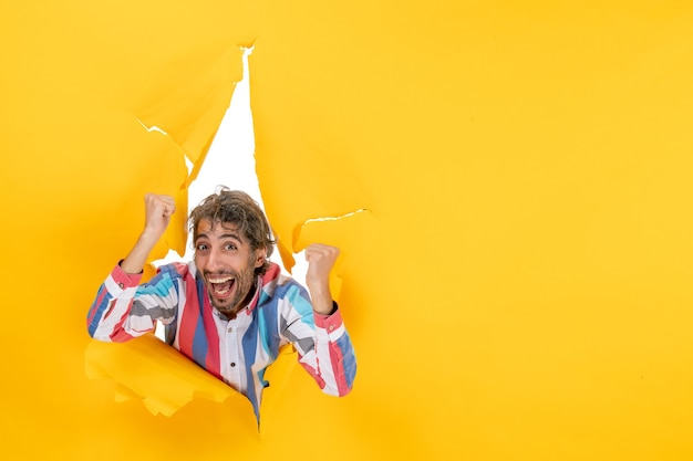 Вид сверху счастливого молодого парня через рваную дыру в желтой бумаге