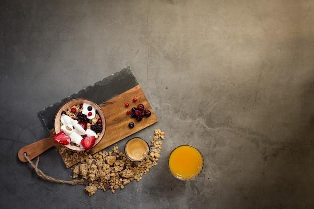 Вид сверху здорового завтрака с мюсли, йогуртом и сезонными ягодами на бетонном фоне