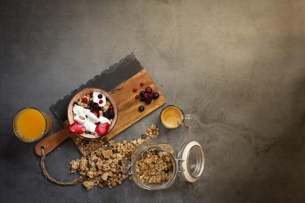ミューズリー、ヨーグルト、季節のベリーをコンクリートの背景に健康的な朝食の上面図