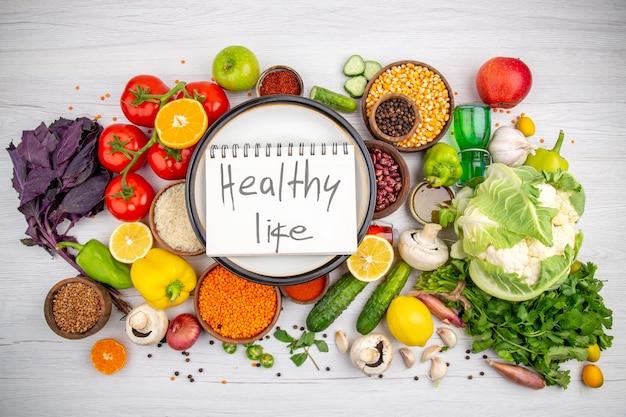 白い背景の上のベジタリアンディナー料理のための新鮮な野菜のコレクションの白い鍋にスパイラルノートの健康的な生活の碑文の上面図