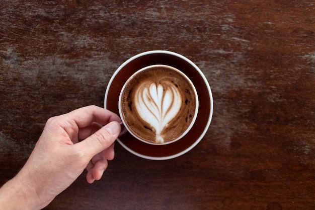 Вид сверху на чашку горячего кофе латте-арт на темном деревянном столе