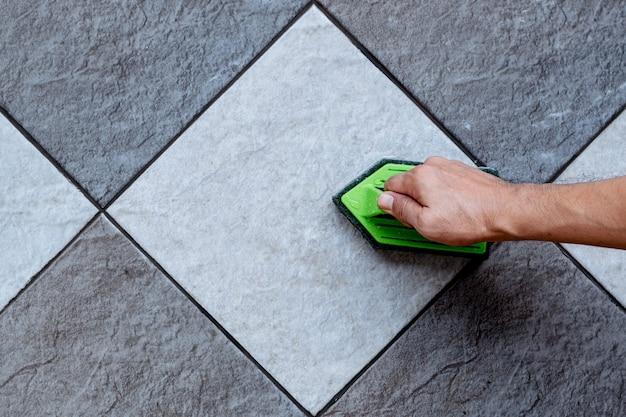 인간의 손에 대한 상위 뷰는 녹색 플라스틱 바닥 수세미를 사용하여 바닥 클리너로 타일 바닥을 문지르고 있습니다.