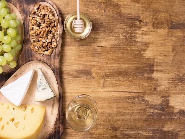 素朴な木製のテーブルの上に新鮮なブドウ、チーズ、ウルナッツを添えた蜂蜜入りの瓶の上面図。利用可能なコピースペース。