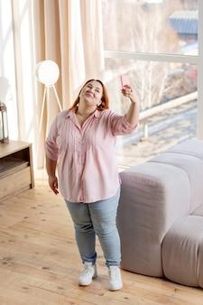 部屋に立って写真を撮るうれしそうな肉付きの良い女性の上面図
