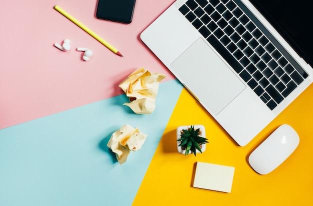 ラップトップコンピューターマウス携帯電話鉛筆サボテンしわくちゃの紙片の黄色、ピンク、青の上面図