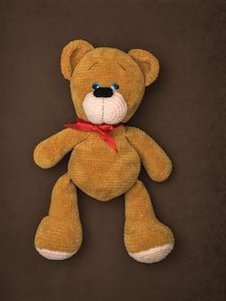 茶色の背景に横たわっている大きなクマの上面図。美しいニットのおもちゃ。