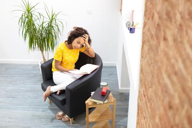 自宅で本を読むことに焦点を当てたラテン女性の上面図。テキスト用のスペース。