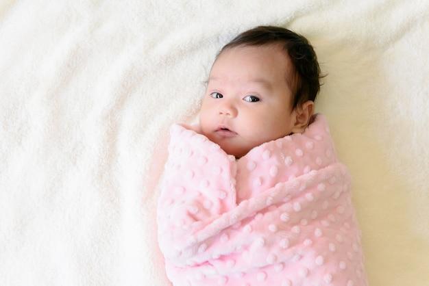 Вид сверху на маленькую симпатичную азиатскую девочку, завернутую в розовую ткань, лежащую на кровати
