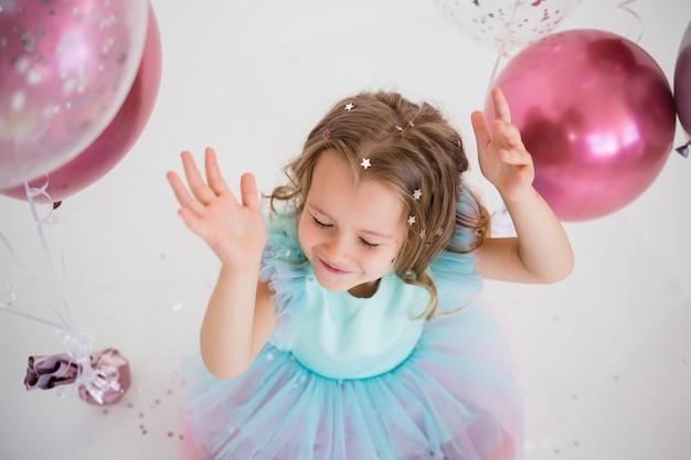 Вид сверху маленькой девочки, ловящей конфетти на белом фоне с местом для текста