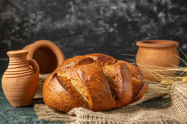 茶色のタオルと暗い表面の陶器の食餌療法の黒いパンのパンの上面図