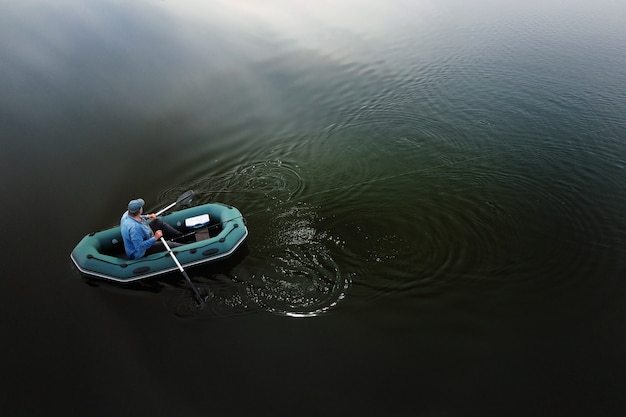 Вид сверху одинокого рыбака на лодке рано утром на рыбалке на озере.
