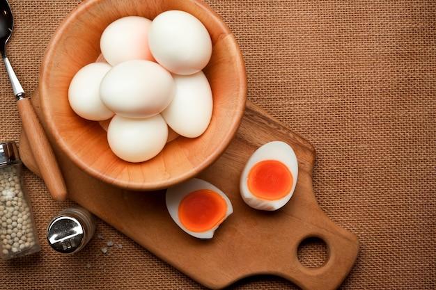 木製のボウルにたくさんのゆで卵と台所のテーブルに半分スライスしたゆで卵の上面図