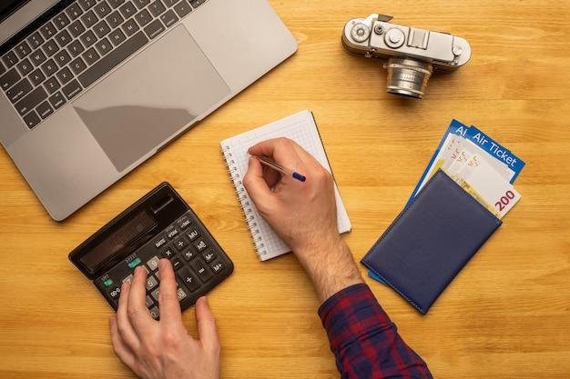 Вид сверху человека, работающего за столом, ведущего подсчет денег на поездку или отдых