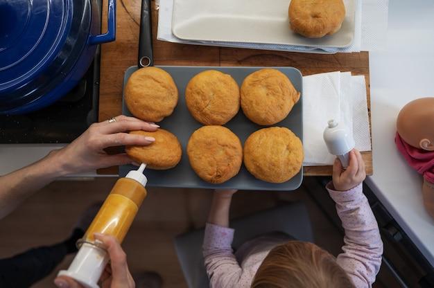 그녀를 돕는 유아 딸과 함께 갓 튀긴 비건 도넛을 잼으로 채우는 어머니의 상위 뷰.