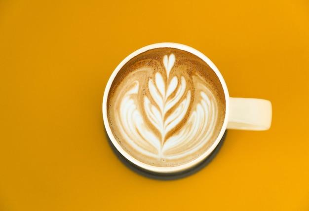 黄色の背景に分離されたラテアートコーヒーのマグカップの上面図。