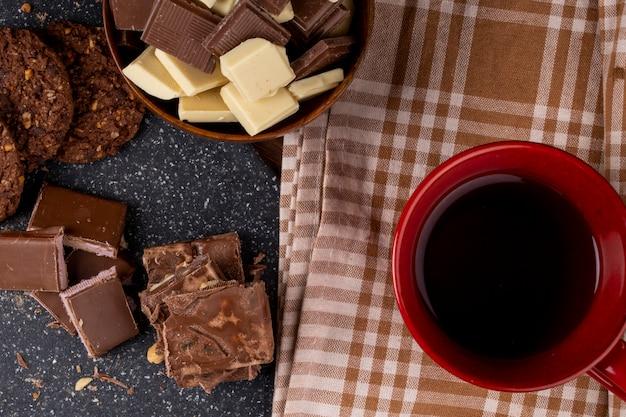 マグカップティーオートミールクッキーと素朴な背景に木製のボウルに暗いと白いチョコレートの部分のトップビュー