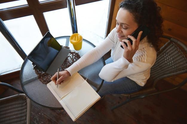 Вид сверху на переговаривающуюся женщину по телефону и запись в дневнике, сидя у окна в деревянном кафе