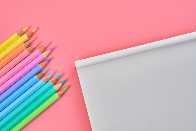 Вид сверху блокнота и цветных карандашей на розовом фоне с копией пространства