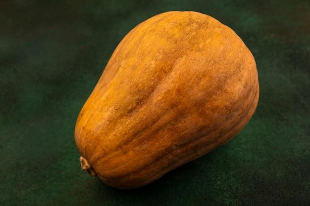 緑の表面に分離された栄養価の高いオレンジ色の野菜カボチャの上面図