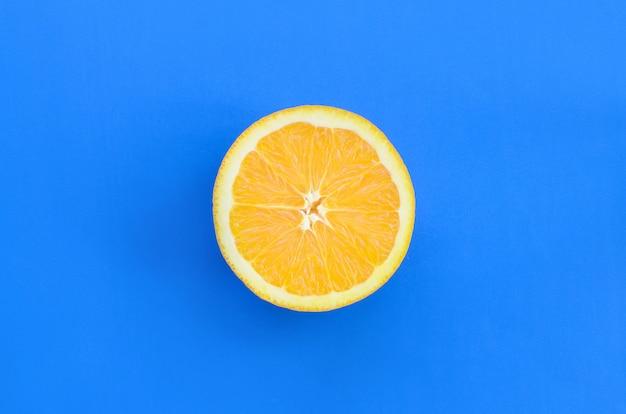 青い色で明るい背景に1つのオレンジ色の果物のスライスの平面図です。飽和柑橘類のテクスチャ画像