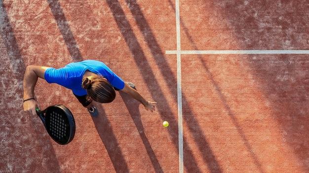 屋外コートでサーブのためにボールをバウンドするパドルテニスプレーヤーの上面図。