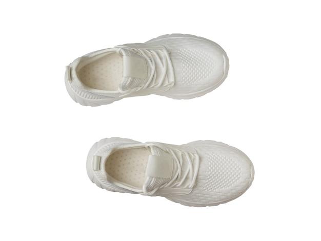Вид сверху пары белых кроссовок, изолированных на белом фоне.