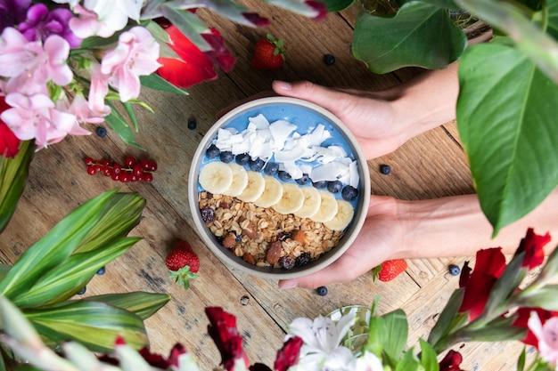 果物とグラノーラと健康的なブルーベリーのスムージーボウルを持っている人の上面図