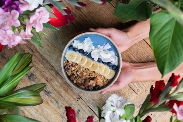 과일과 그래놀라를 곁들인 건강한 블루베리 스무디 그릇을 들고 있는 사람의 꼭대기