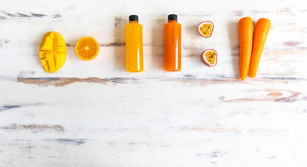 素朴な木製のテーブルの上にリンゴのニンジンオレンジとマンゴーの場所の周りに果物と野菜ジュースのプラスチックボトルの上面図。健康的な飲み物、デトックス、ダイエットの概念。